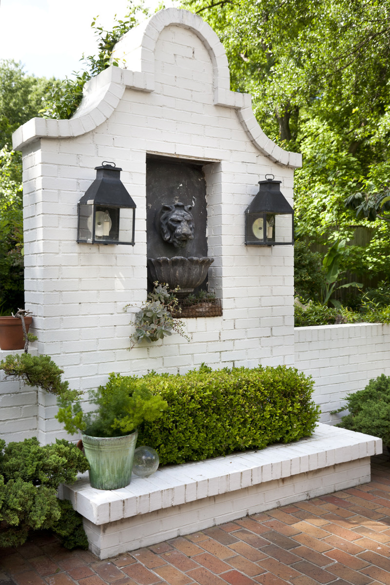 The white-painted brick wall dividing patio from driveway has a lion's head fountain and twin black-iron lanterns.