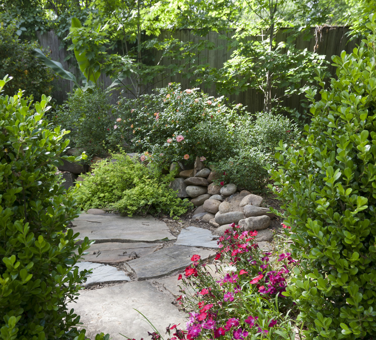 "A flagstone path is lined with dianthus, also known as "" garden pinks,"" an English favorite for centuries."
