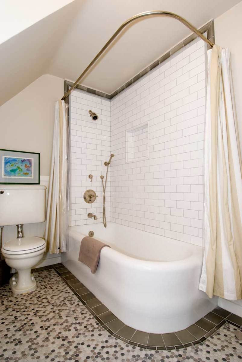 A streamlined tub and vintage toilet are original; the expertly tiled border, penny-round floor, and subway tile are more recent upgrades. Photo: Chris Considine