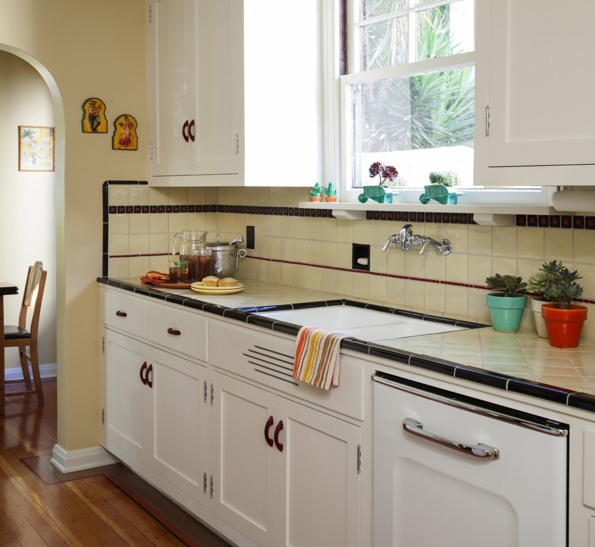 This installation from Native Tile looks authentic to the late 'teens or early 1920s. Cream-color square tiles are laid on the diagonal on the counter and in straight rows on the backsplash,  accented with two feature strips and black perimeter bands.  Photo: Edmund Barr