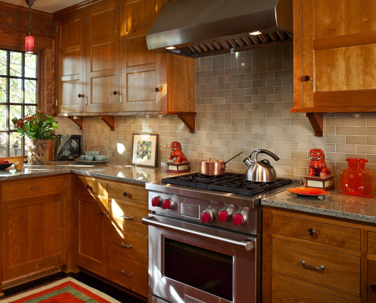 Pale olive-green subway tiles by Mission Tile West complement the red birch cabinets in a kitchen by David Heide Design Studio. Photo: William Wright