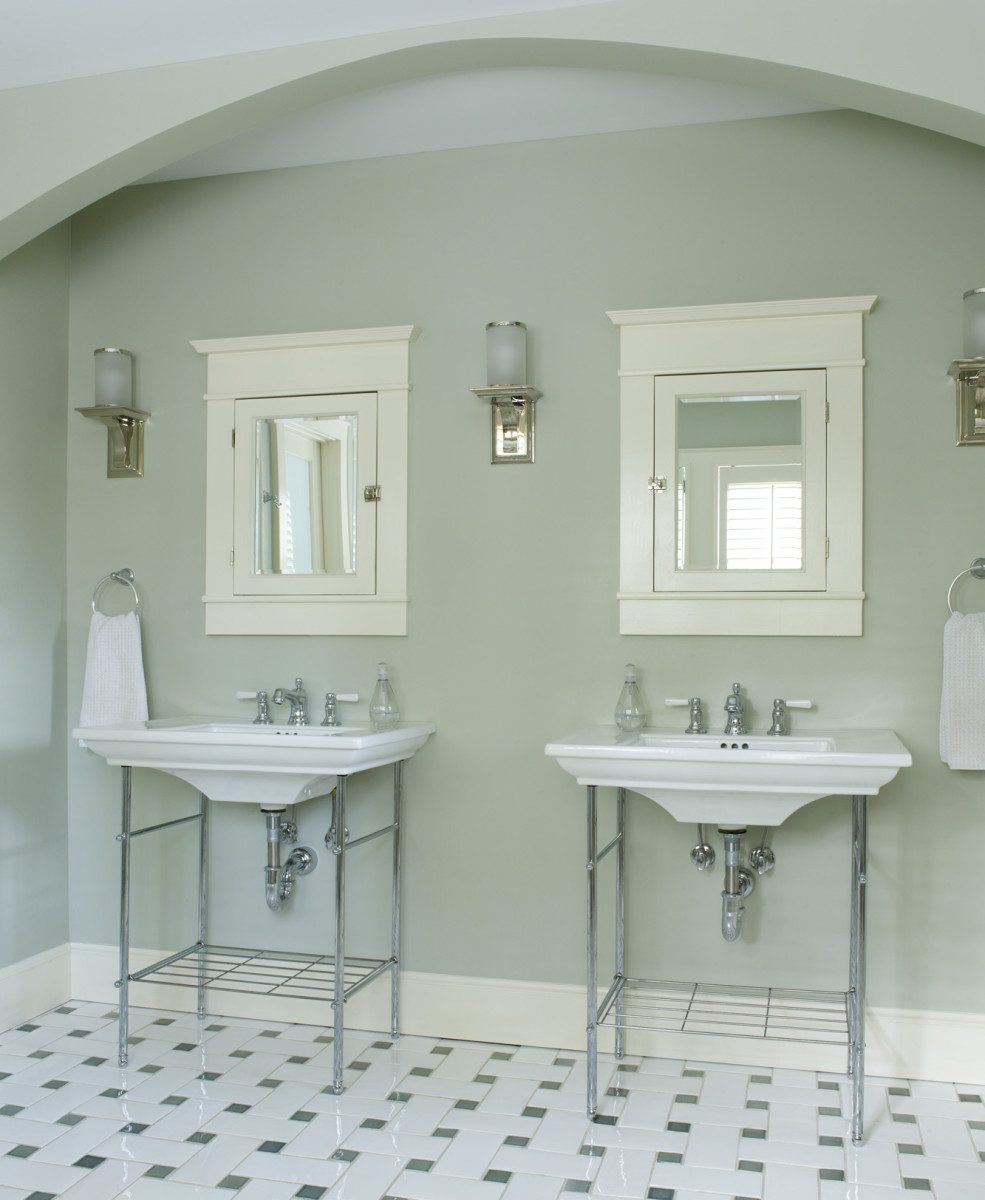 Gentle green softens utilitarian surfaces in the master bath, where zones include this sink arch.