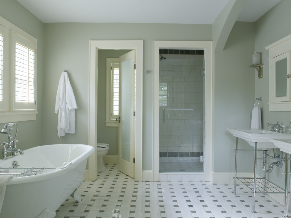 The layout includes a soaking tub, a separate shower, and a WC behind a door inset with frosted glass. The large-scale tile floor has an Art Deco vibe.