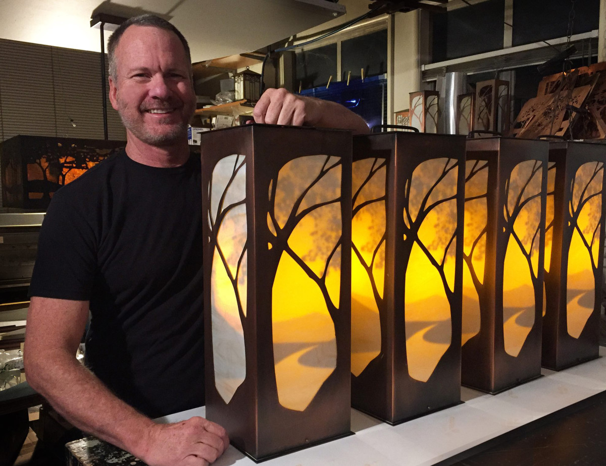 James Mattson with a row of custom lanterns; the interior silhouette of a sunset over a landscape is visible only when the lanterns are lit.