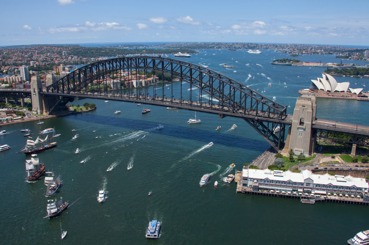 Historic vessels pass under the Sydney Harbour Bridge on Australia Day.