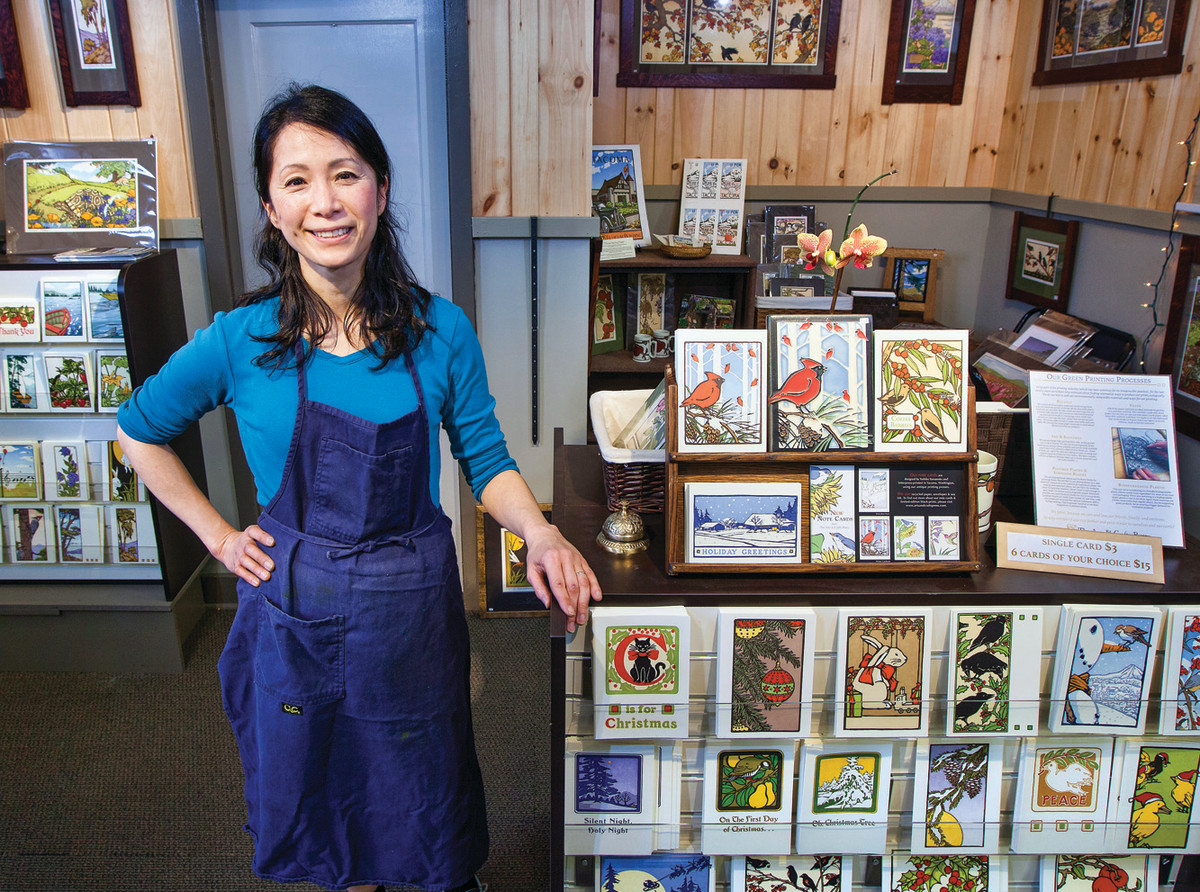 Yoshiko Yamamoto stands before some of her many note-card designs. She is moving toward more eco-friendly printing methods.