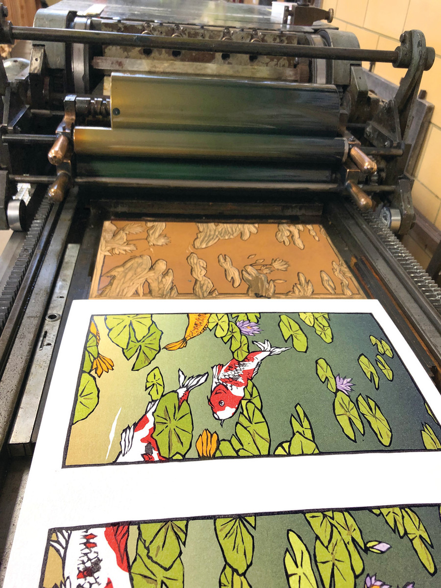 """Waterlilies II,"" a triptych of koi swimming though lily pads, is seen on the press. The 19 individual colors must be impressed on the paper using one color/one block at a time."