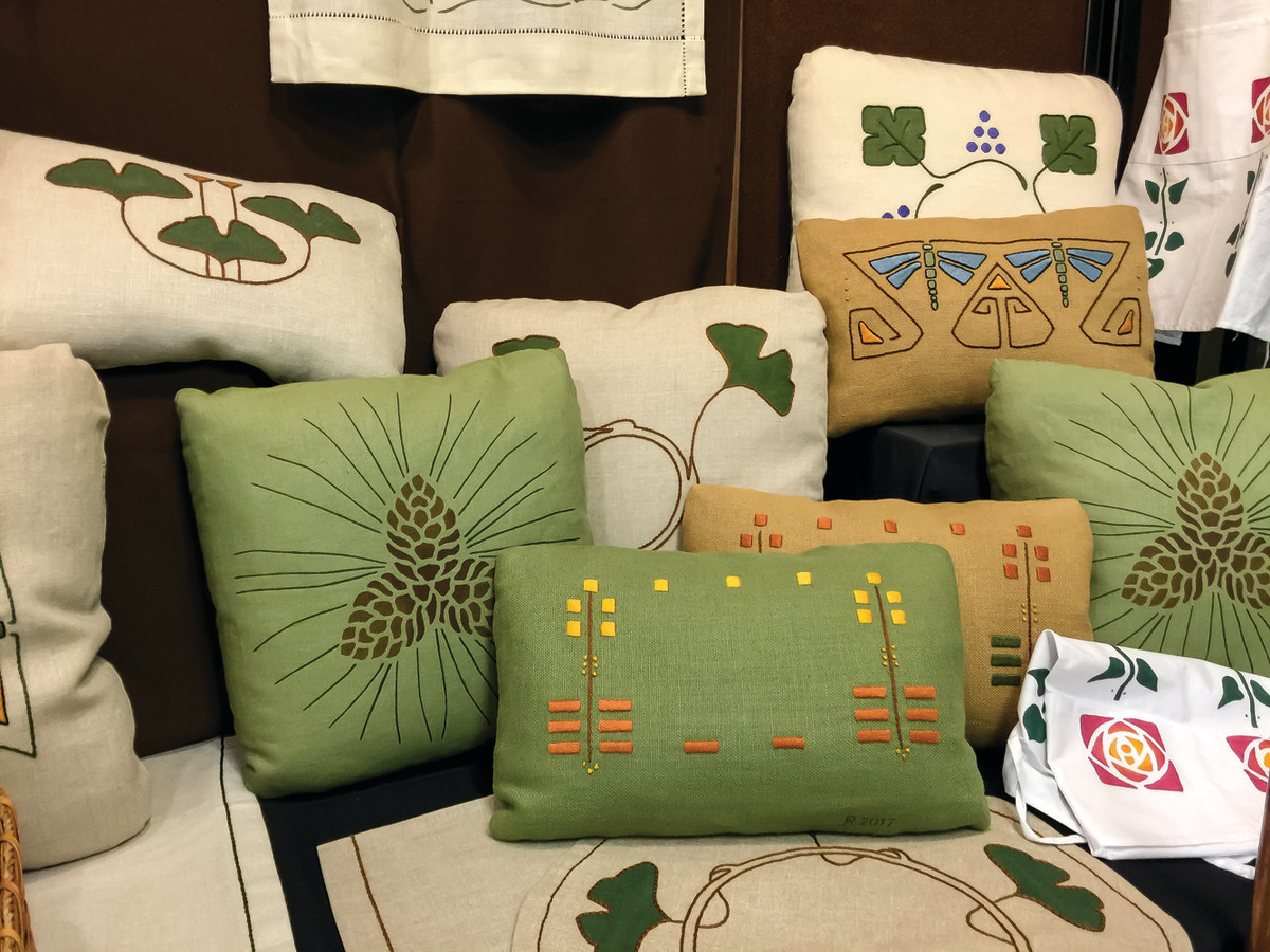 A group of finished pillows includes early and more recent designs.