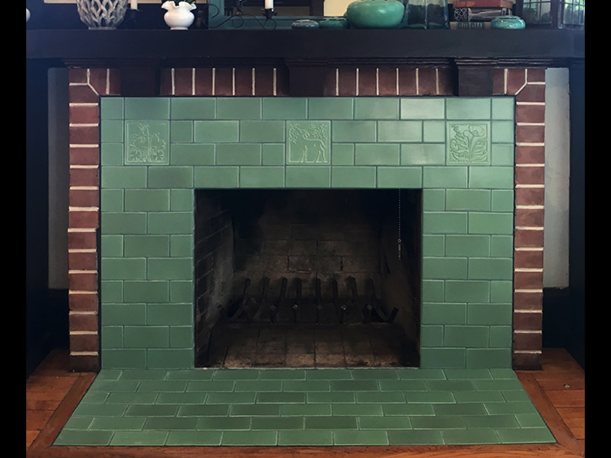 This Carreaux du Nord fireplace surround has green field tiles with 3 decorative (or deco) accent tiles toward the top.