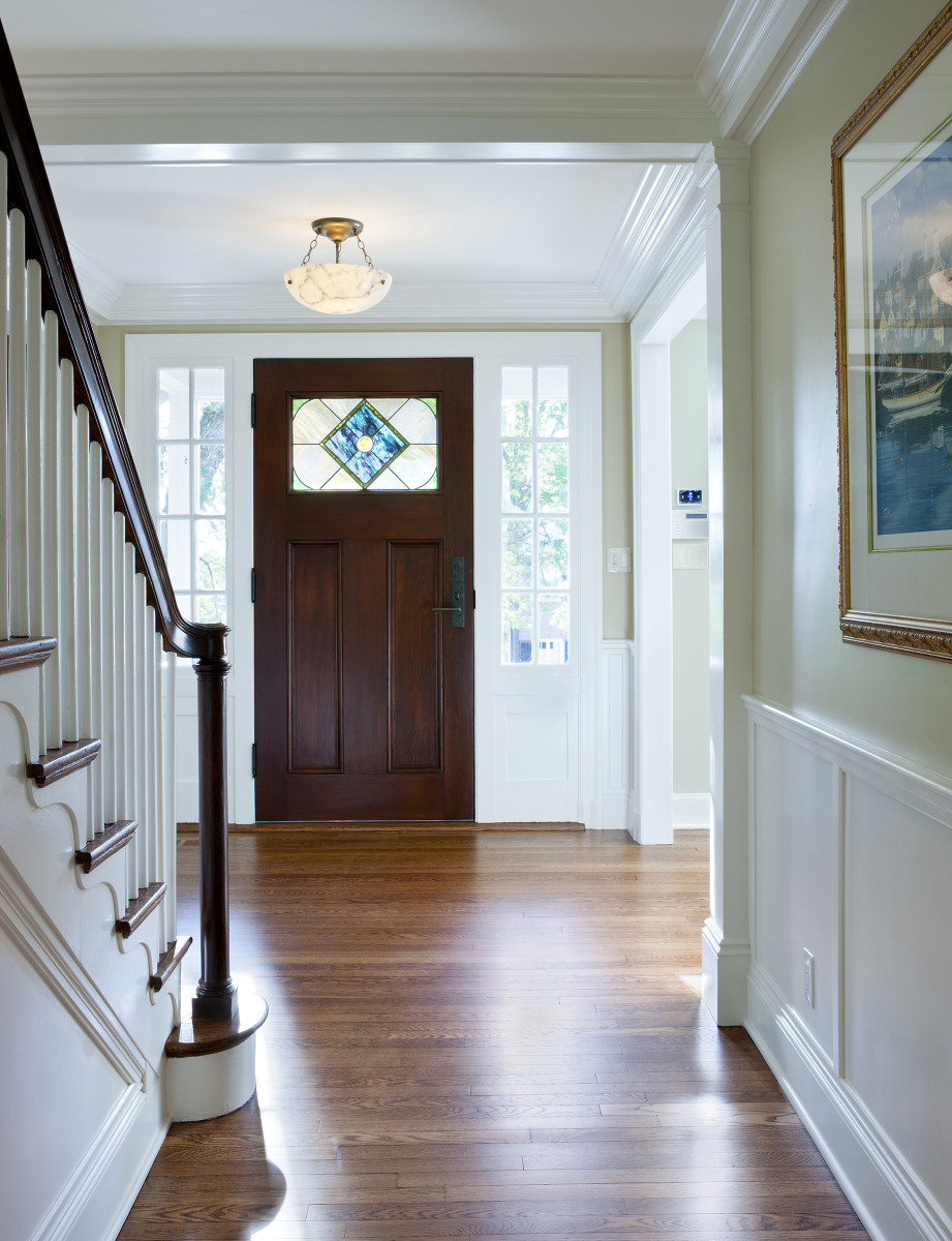 An art-glass panel and sidelights add formality to the entry; the alabaster light fixture is vintage.