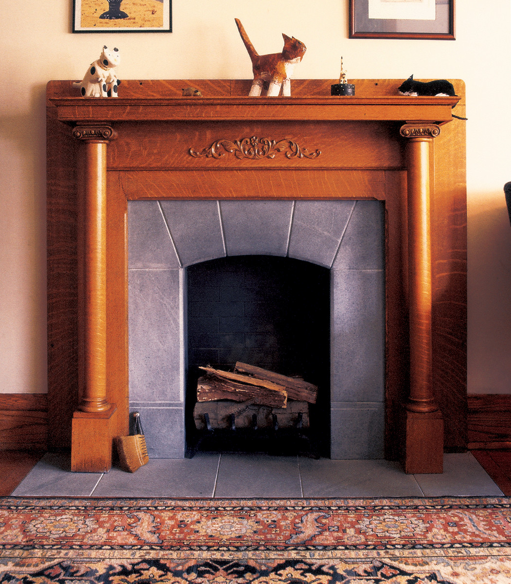 A soapstone fireplace with a gentle sunburst arch, from Vermont Soapstone.
