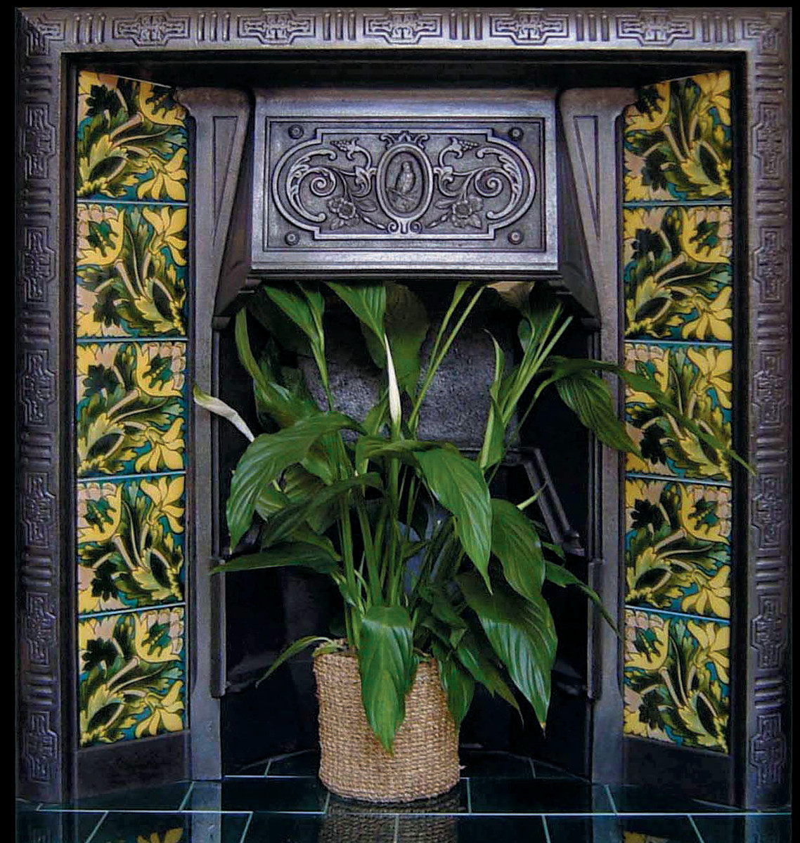 Floral Aesthetic fireplace tiles from Tile Source dress the legs of a coal grate-style surround.