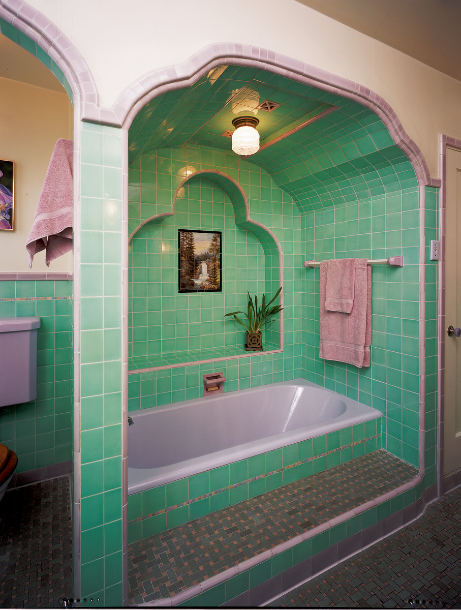 This tub recess has a sunken bathtub in a raised platform, all in candy pink and green tiles.