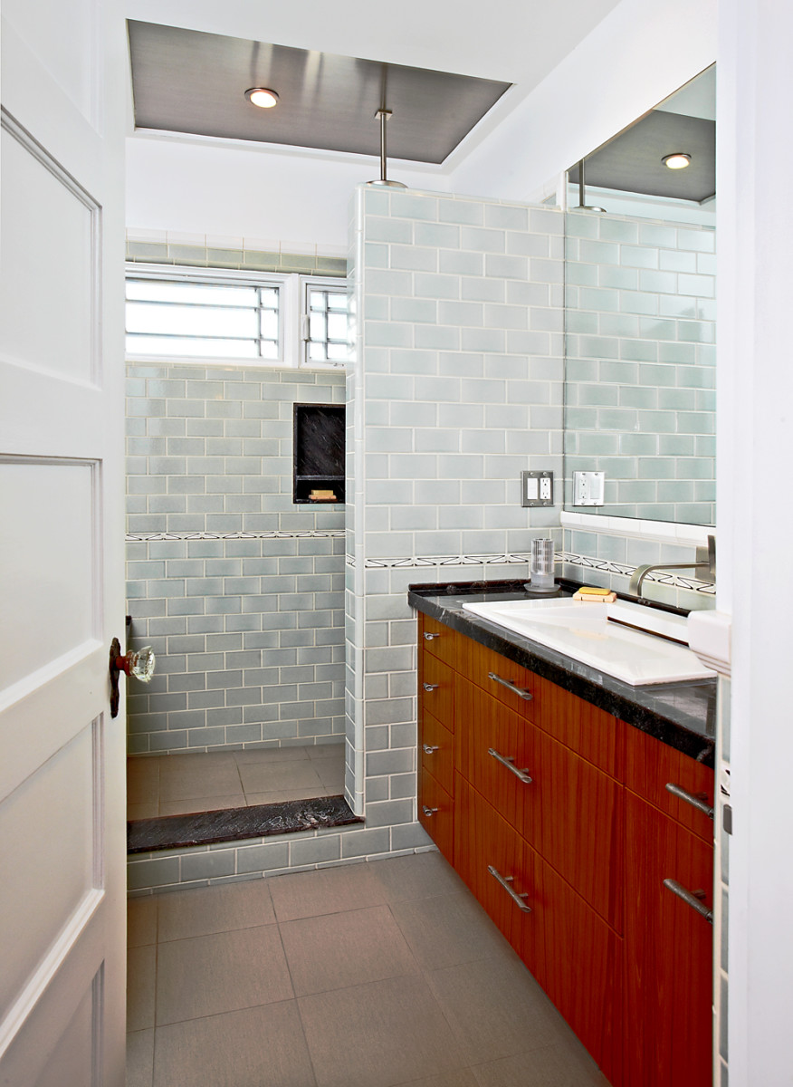 Retaining (but moving) the narrow door allowed a bathtub to fit behind the door, along with a walk-in shower in this 7x9-foot space.