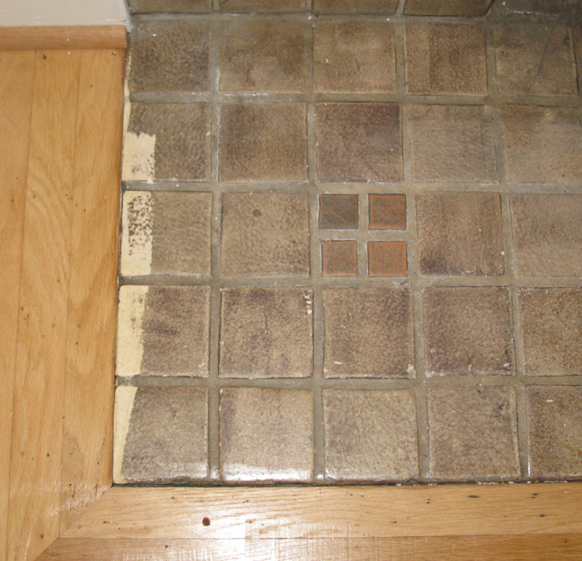For hearth tiles damaged by a floor sander, a little patching was followed by meticulous painting and blending.