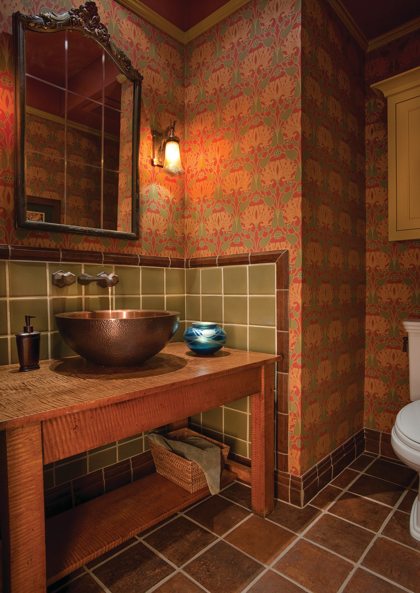 Rich and textural, this powder room with copper, wood, and wallpaper is a cozy example of Arts & Crafts Revival design.
