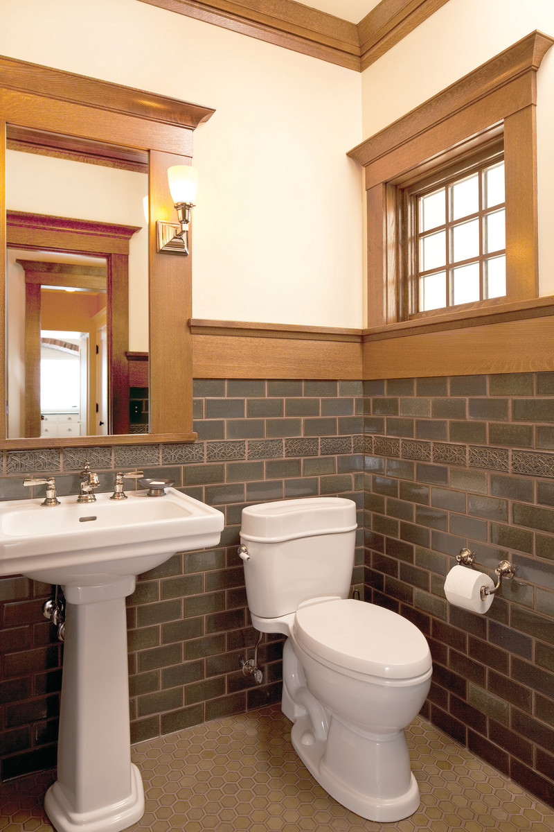 Unlike white-tile bathrooms upstairs, this revival powder room matches the Arts & Crafts-era trim and coloring of the living rooms.