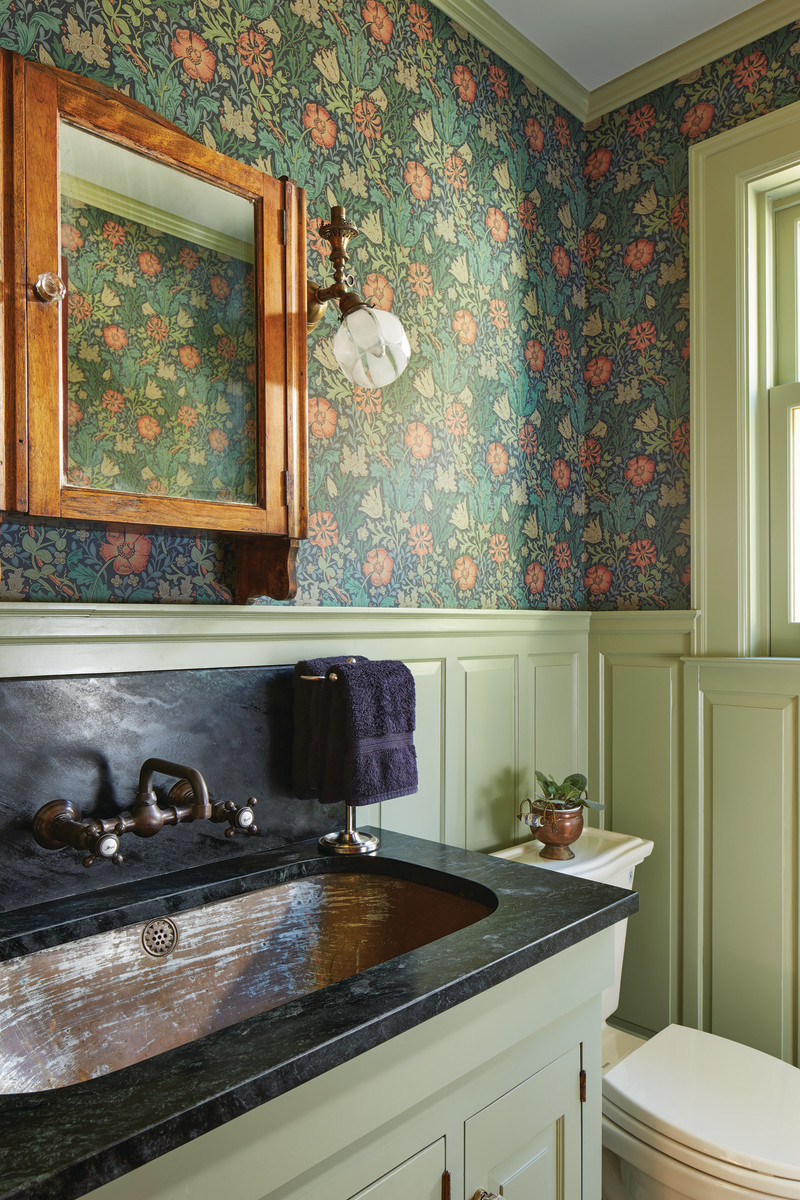 A rescued butler's sink found new life in a half-bath fitted with raised-panel wainscoting and a Morris-design paper.