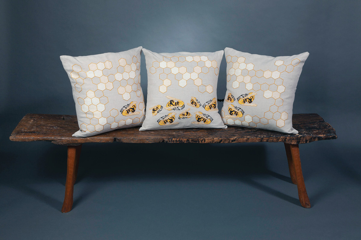 A grouping of pillows from the End of Pollinator series forms a three-dimensional triptych, on a bench made by colleague Keith Wiesinger.