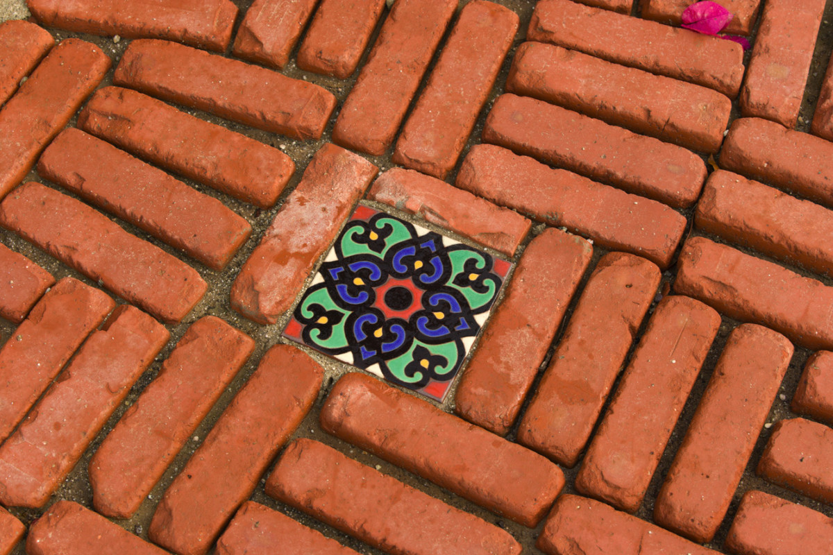 The courtyard floor is made up of concrete pavers, old bricks, and pottery shards.