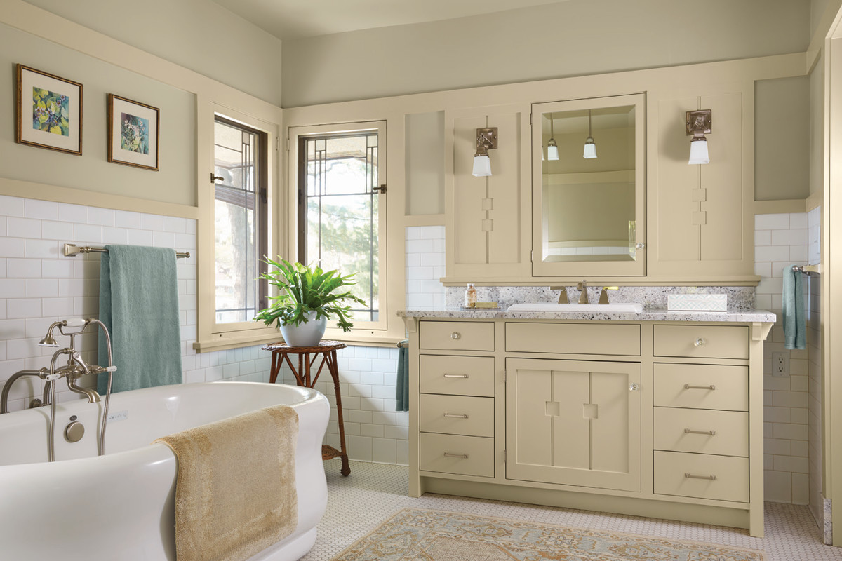 In the master bath, the sink-cabinet doors pick up a detail seen in the original windows. White tile, flat trim work, and the curvy tub add to the period look.