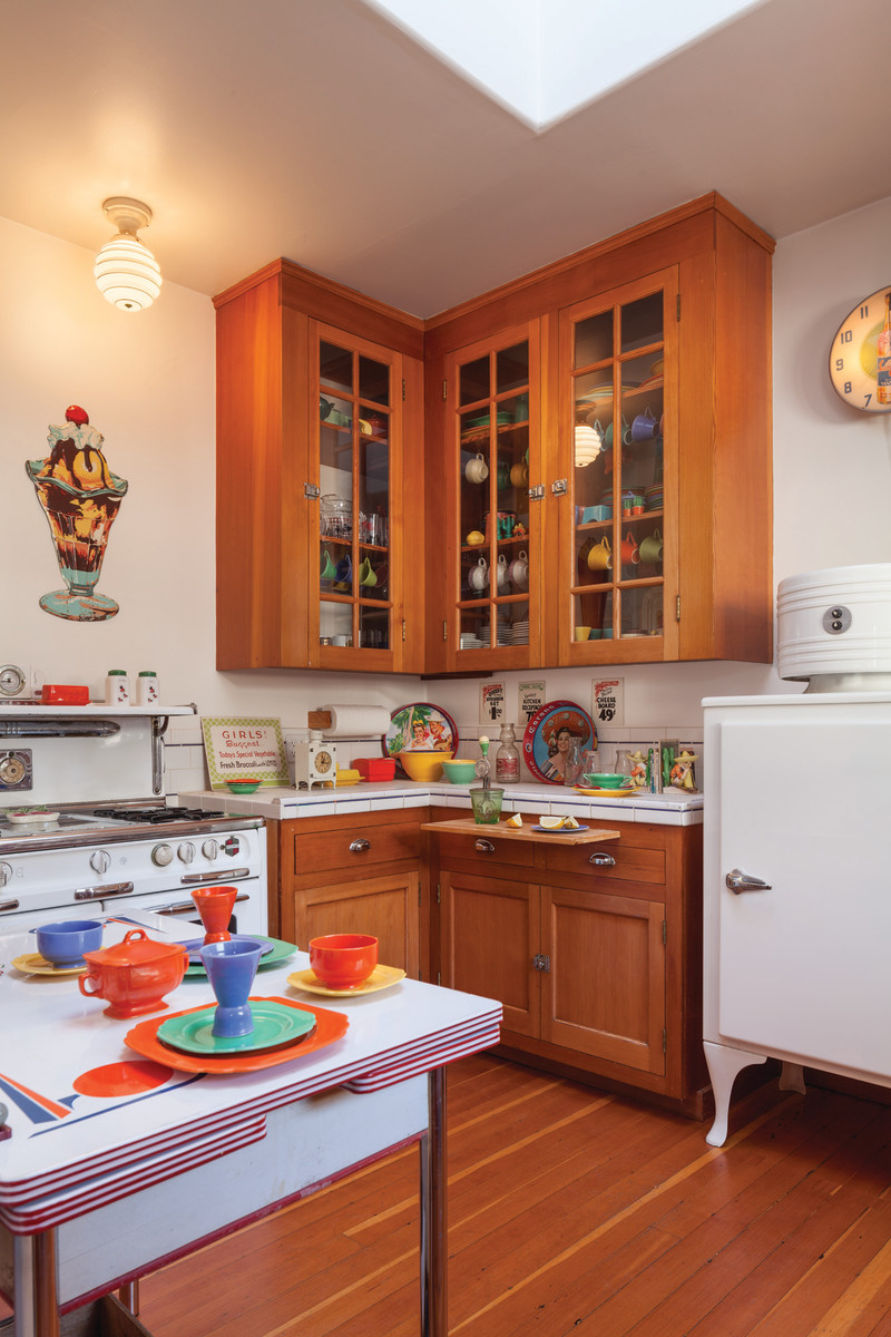 A previously remodeled kitchen was taken down to the studs and refitted with period fir cabinets; the original fir floor was uncovered and refinished. Collectibles include Fiesta dinnerware. Vintage appliances are in working order.